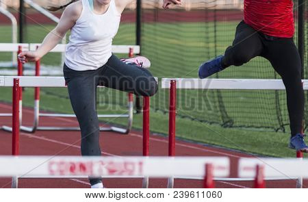 Two High School Girls Are Racing Each Other In The 100 Meter High Hurdles During A Track And Field C