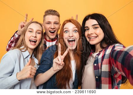 Group of smiling school friends taking a selfie while having fun together over yellow background
