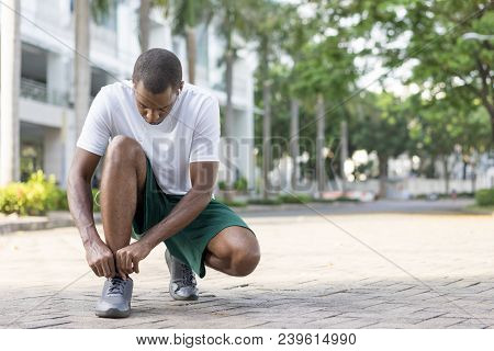 Black Sportsman Getting Ready For Morning Run Down Walkway. Young Afro American Man Tying Shoelaces