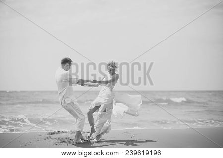 Beautiful Happy Young Wedding Couple Of Man And Woman In White Spinning On Ocean Beach Coast On Wind