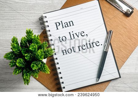 Plan To Live Not Retire. Inspirational Quote On Notebook With Pen, Clipboard And Potted Plant.
