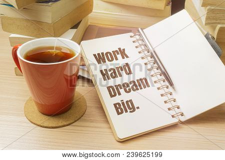 Work Hard Dream Big. Inspirational Quote On Notebook With Pen, Cup Of Tea And Pile Of Books.