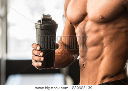 Man With Perfect Body Holds Protein Shaker In The Gym After Workout