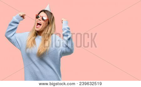 Young woman celebrates birthday happy and excited celebrating victory expressing big success, power, energy and positive emotions. Celebrates new job joyful