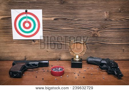 Best Shooter Award Background With Copy Space. Winner In Shooting. Gun, Paper Target And Gold Medal.