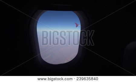 Mountain Range From The Airplane Window. Airplane Wing. Aerial View On Mountains Through Window Of A