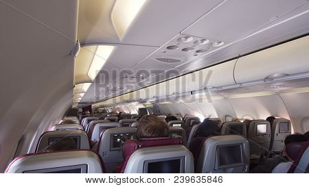 Aircraft Cabin With Rows Of Seats. Interior Passengers Airplane With People On Seats. Passengers Tra