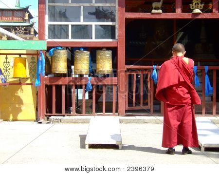 Buddhist Monk Wearing Red Bowing Head In Prayer At A Temple