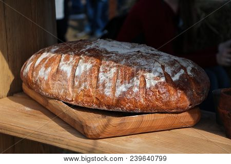 Freshly Baked Bread In Rustic Bakery With Traditional Oven On The Brown Wooden Table In The Sun And