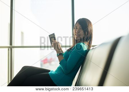 Asian Woman Passenger Holding Passport And Checking Flight Or Online Check In And Travel Planner At