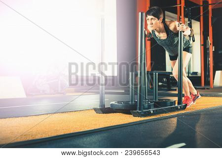 Active People Sport Workout Concept. Motivating With Copy Space. Attractive Woman Moving Big Weight.
