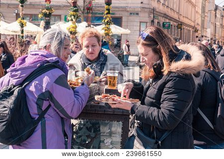 Krakow, Poland, April 2, 2018, Three Old Women Eat Street Food And Drink Beer On The Street During T