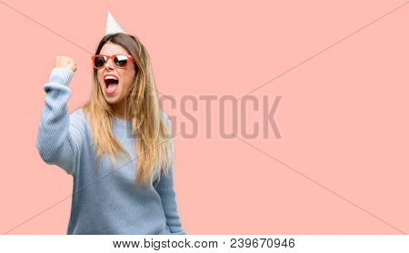 Young woman celebrates birthday irritated and angry expressing negative emotion, annoyed with someone
