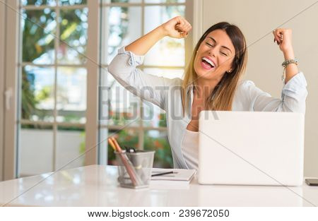 Student woman at table with laptop at home happy and excited celebrating victory expressing big success, power, energy and positive emotions. Celebrates new job joyful