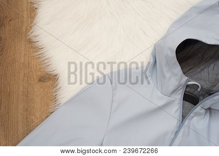 Women Blue Rain Jacket With A Hood On A Wooden Background. Concept Of Fashion And Design, Shopping
