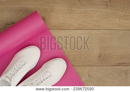 Pink Yoga Mat And White Trendy Sneakers On A Wooden Background. Fitness Concept, Active Lifestyle, B