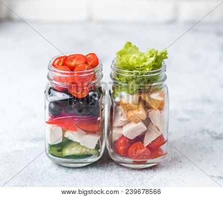 Greek Salad And Caesar Salad In Glass Mason Jar On Gray Background.homemade Healthy Caesar Salad And