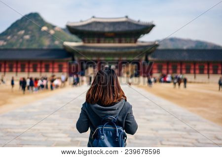 Young Asian Woman Traveler With Backpack Traveling Into The Gyeongbokgung Palace  With Blue Sky And