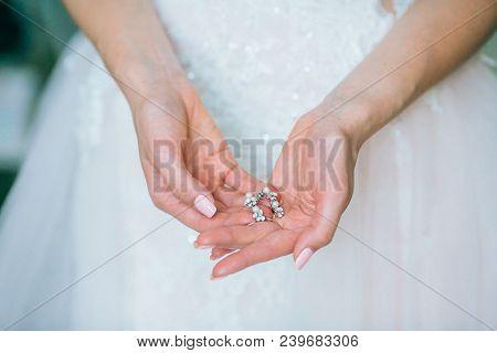 Elegant Bride Hanging Silver Earrings. Tender Bridal Hands With Accessories. Morning Bridal Preparat