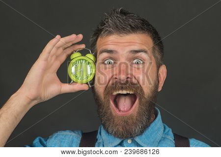 Bearded Smiling Man With Alarm Clock On Black Background. Macho Holding Alarm Clock Near Face. Happy