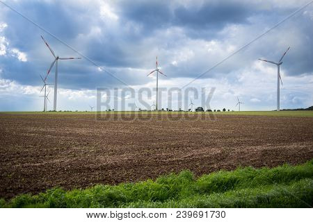 Wind Turbines For Generating Electricity On A Field In Nature