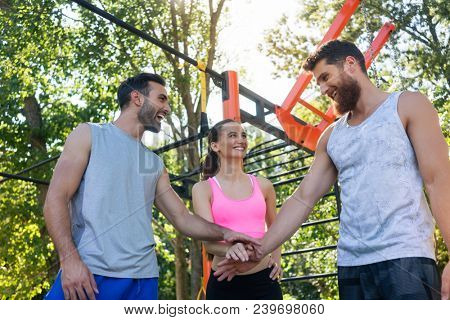 Low-angle view of three cheerful young friends putting hands together as a gesture of determination and motivation for starting street workout together in summer