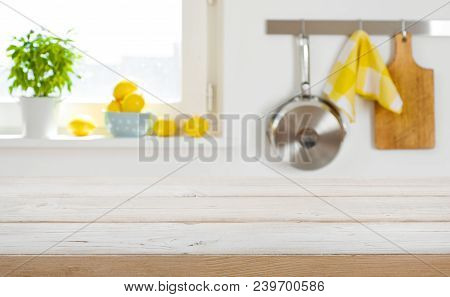 Blurred Kitchen Interior Background With Wooden Table Top In Front