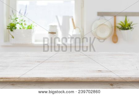 Wooden Table Top Over Blurred Kitchen Interior With Copy Space