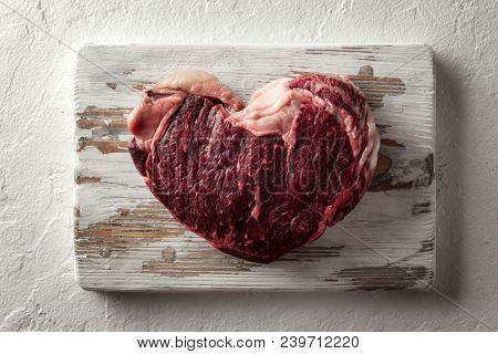 Marbling heart shape ribeye steak on white wooden plate. Prime rib beef chop