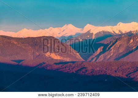 Aerial View Of Mountains With Snowy Peaks In The Light Of The Setting Sun, Sochi, Russia