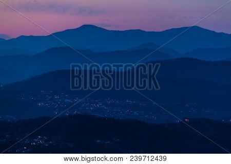 Aerial View Of The Dark Mountains And Illuminated Villages Of Sochi In The Dusk, Russia
