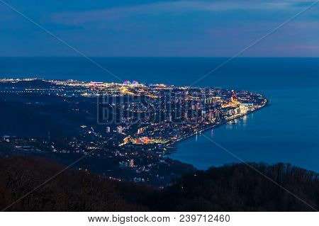 Beautiful Aerial View Of The Illuminated City Of Sochi And The Sea From The Peak Of Mount Akhun In T
