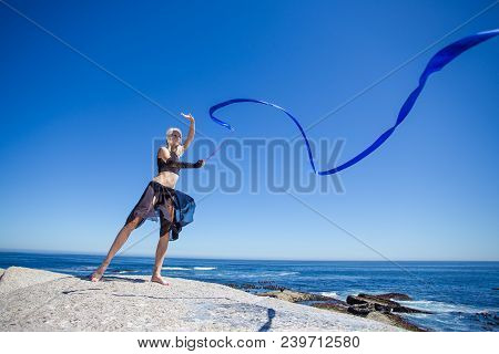 Beautiful Female Fitness Model Doing Ribbon Dancing On A Granite Rock Overlooking The Ocean On A Bri