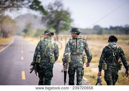 Asian Army Soldier Return To Base After Completing Military Mission. Armed Infantry Walking In The F