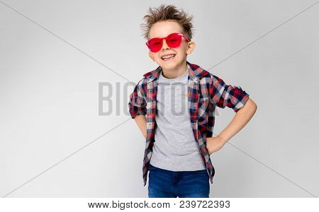 A Handsome Boy In A Plaid Shirt, Gray Shirt And Jeans Stands On A Gray Background. A Boy In Red Sung