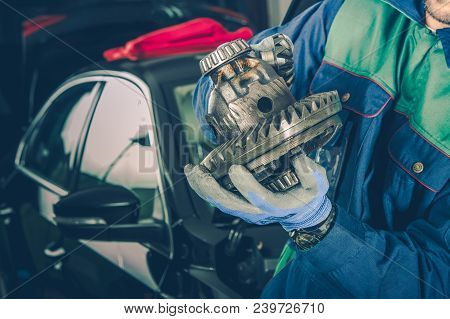 Caucasian Car Mechanic In His 30s With Part Of Car Differential In Hands. Vehicle Service Theme.