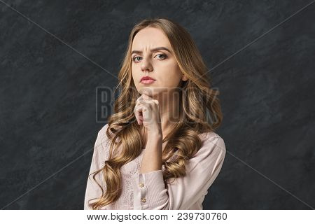 Pensive Young Woman Touching Her Chin. Thoughtful Girl With Suspicious Look Thinking About Something