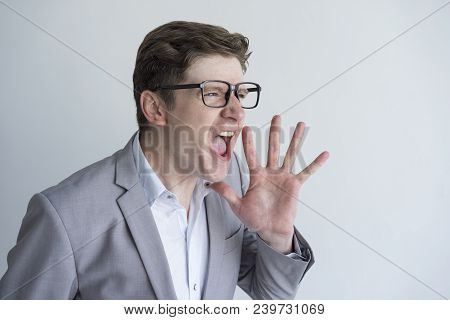 Angry Emotional Businessman Screaming Aside And Holding Hand Near Mouth. Aggressive Emotionally Dist