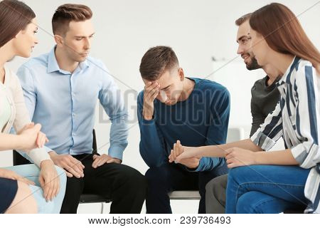 People supporting man at group psychotherapy session indoors