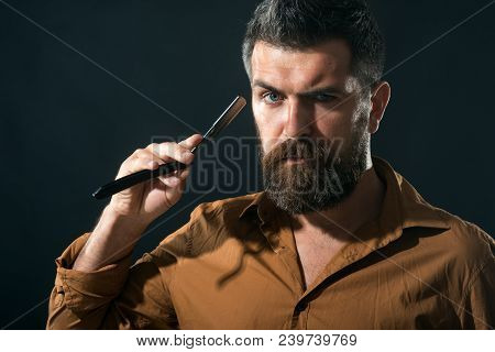 Handsome Bearded Hairdresser In Stylish Clothes Holding A Dangerous Razor. Bearded Attractive Macho