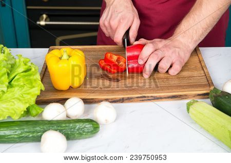 Vegetables Getting Cut On Wooden Cutting Board. Hand Slice Pepper With Ceramic Knife. Food Preparati