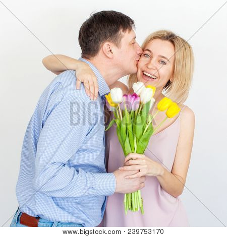 Man gives a bouquet of flowers to woman. Husband gives a gift to his wife. Mother's day. Valentines day