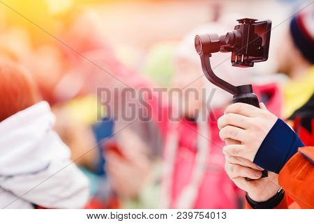Close-up Of Man Shoots Video On Phone Using An Image Stabilizer.