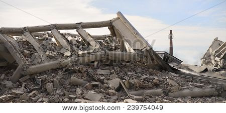 Industrial concrete building destructed by strike. Disaster scene full of debris, dust and crashed buildings. poster