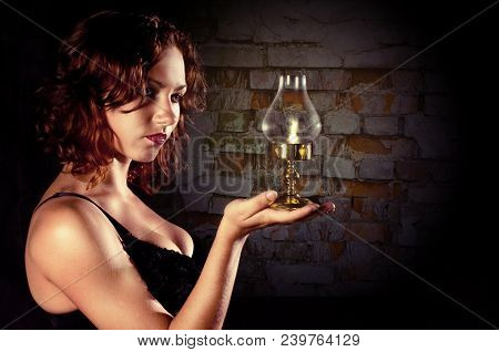 Young Girl In A Black Corset Holds A Retro Lantern In A Dark Old Abandoned Basement