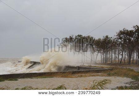 A Hurricane At Sea. Large Waves Through A Concrete Parapet