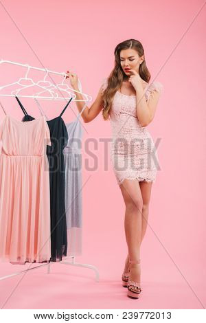 Full length photo of doubting young woman 20s thinking and choosing dresses on clothing rack isolated over pink background poster