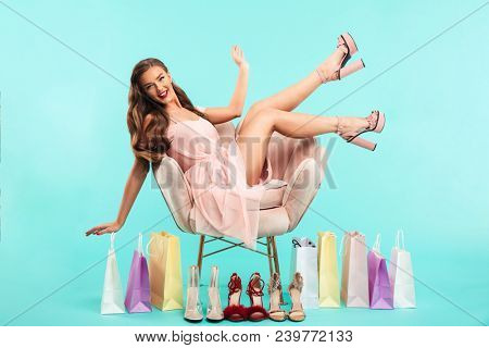 Portrait of charming woman 20s sitting on pink armchair after shopping with lots of purchase bags isolated over blue background poster