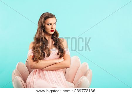 Image of naughty woman in pink dress sitting in armchair with arms crossed and looking aside in resent or offense isolated over blue background