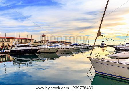 Luxury Yachts And Motor Boats At Sunset. Sailing Boats Docked At Pier In Marina In Sunshine, Blue Wa